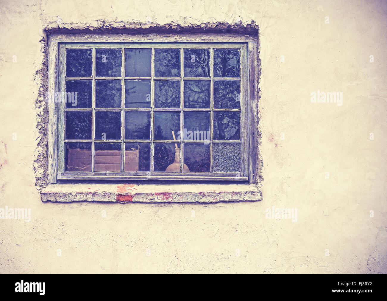 Old grungy window on an old dirty wall, retro filtered. - Stock Image