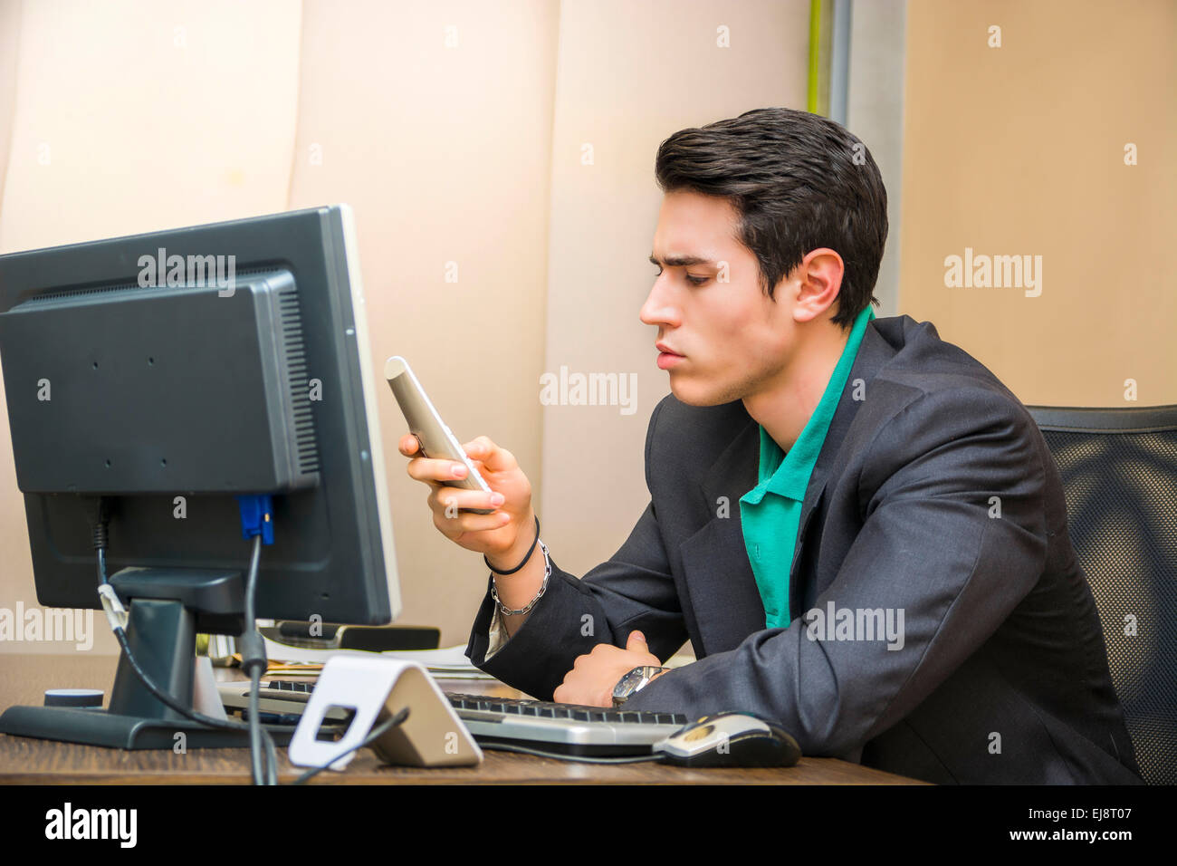 Handsome young businessman at desk in his office dialing on phone to make a call Stock Photo