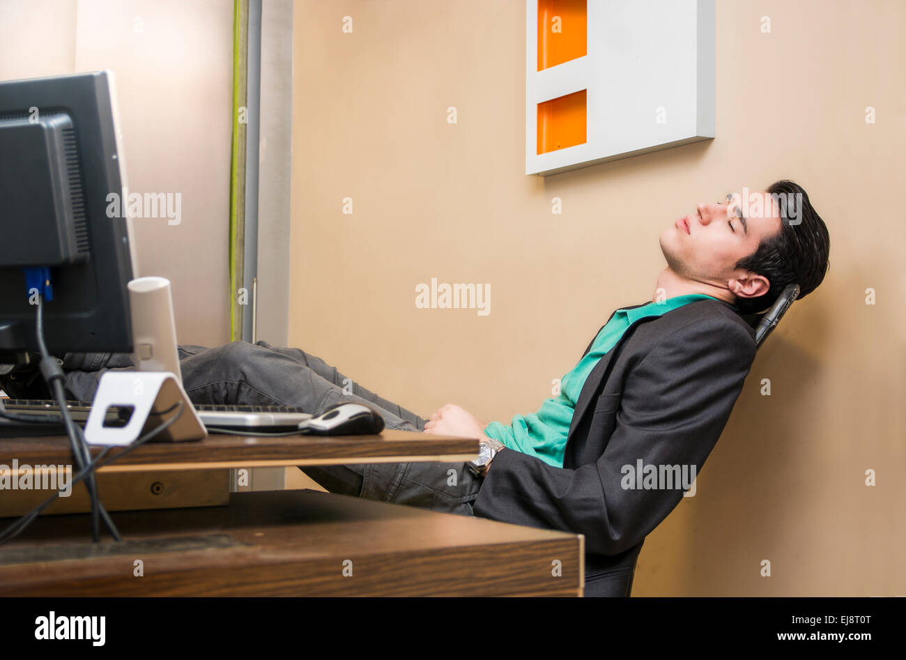 Overworked, tired young businessman sleeping at his desk  in office, in front of computer - Stock Image