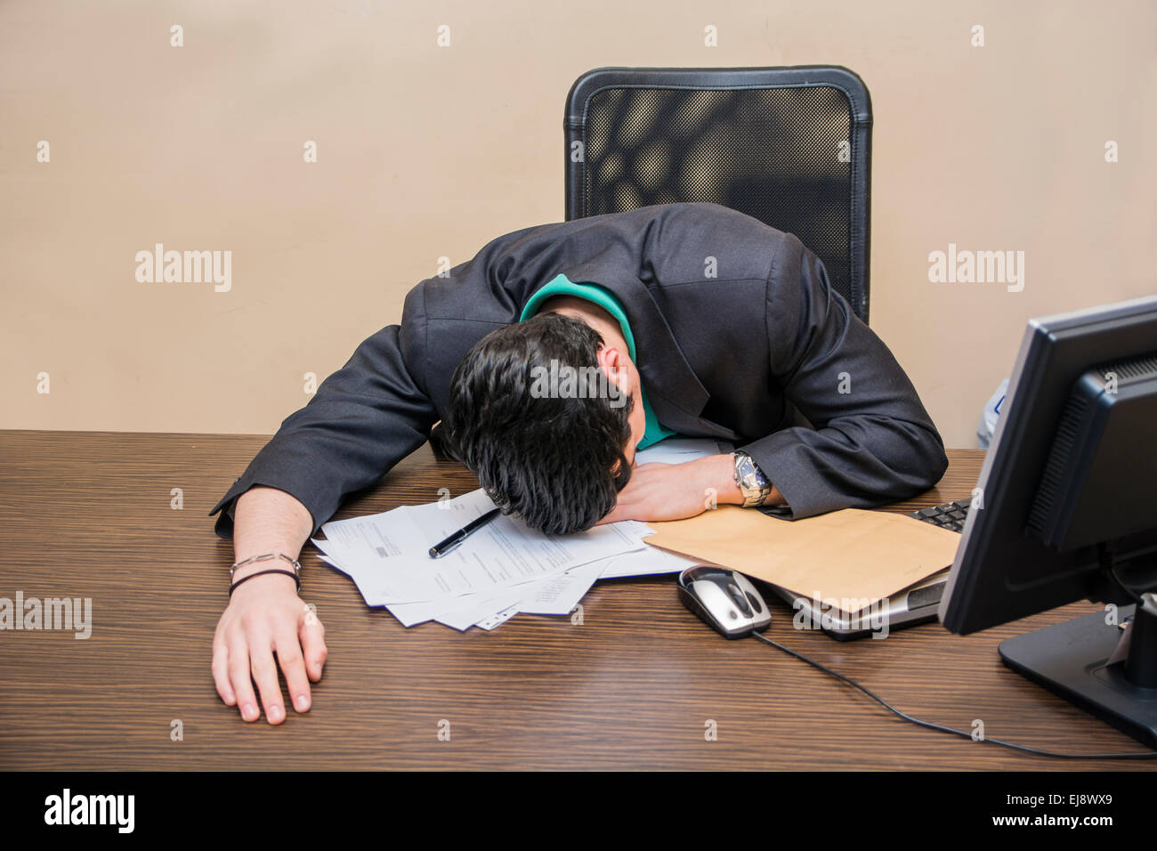 Overworked, tired young businessman sleeping on his desk  in office, in front of computer over some documents - Stock Image