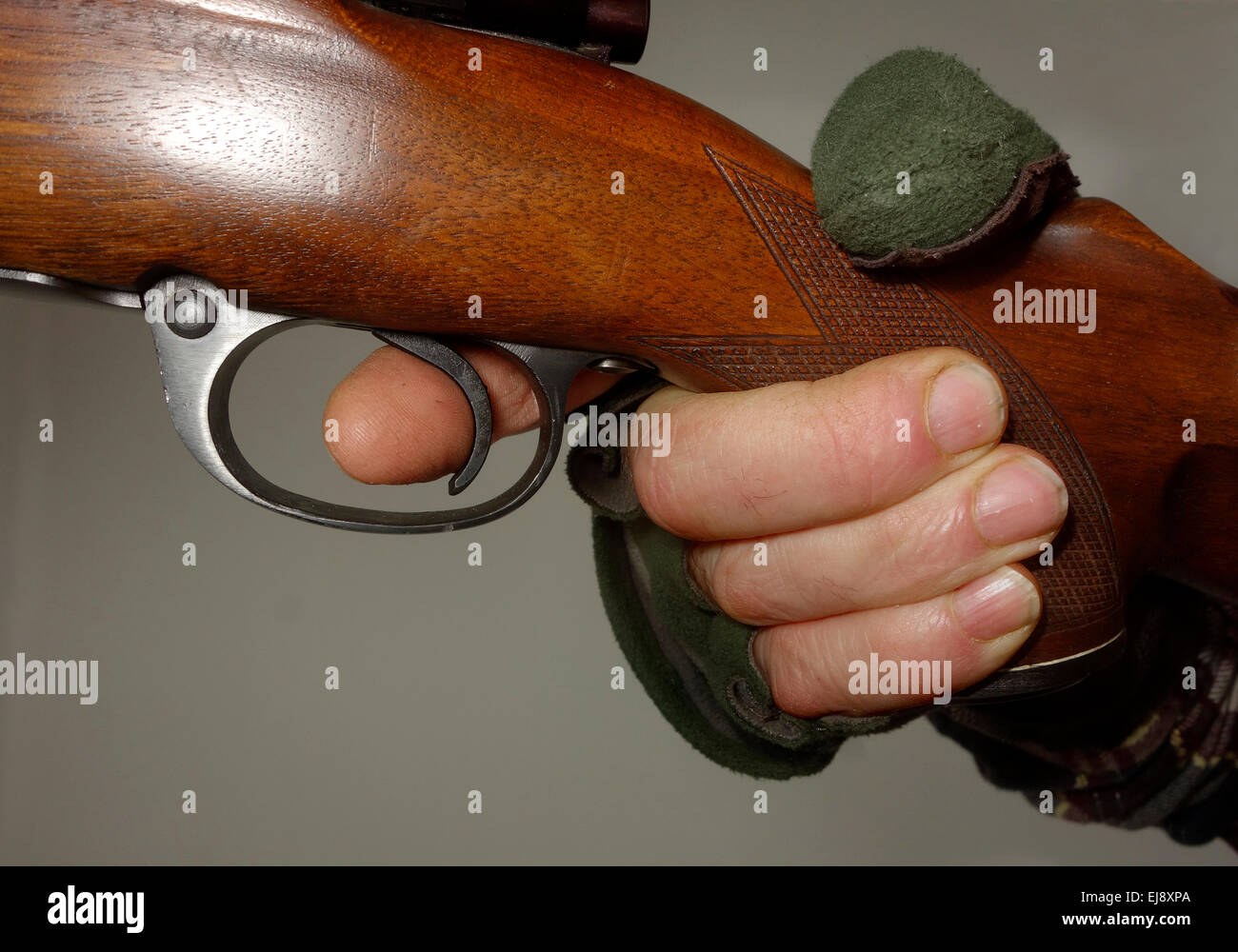 Close up of an index finger on the trigger. - Stock Image