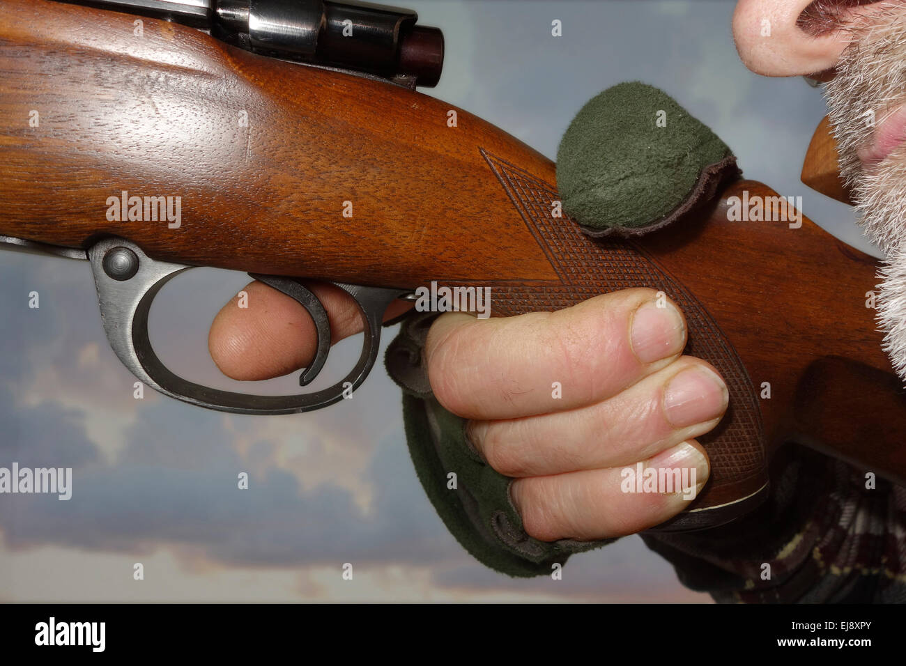 Close up of an index finger on the trigger and a hunter who is about to shoot the riffle. - Stock Image