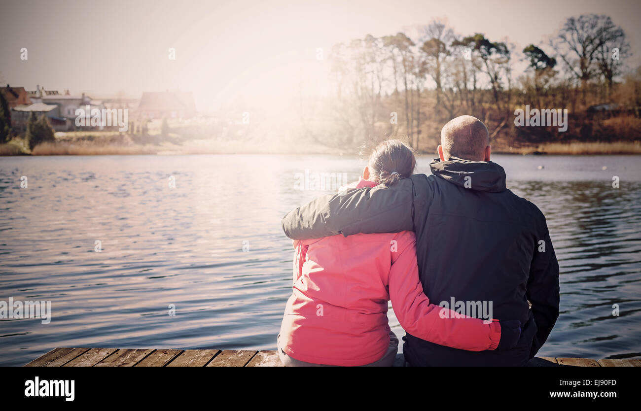 Retro filtered photo of a couple sitting on wooden pier by lake. - Stock Image