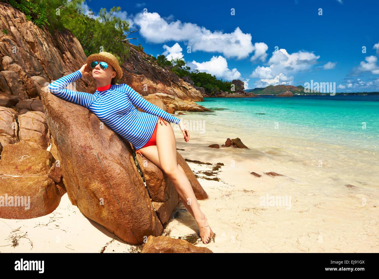 Woman at beautiful beach wearing rash guard - Stock Image