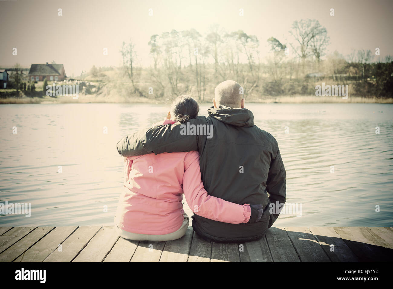 Retro sepia stylized picture of a couple sitting on wooden pier by lake. - Stock Image