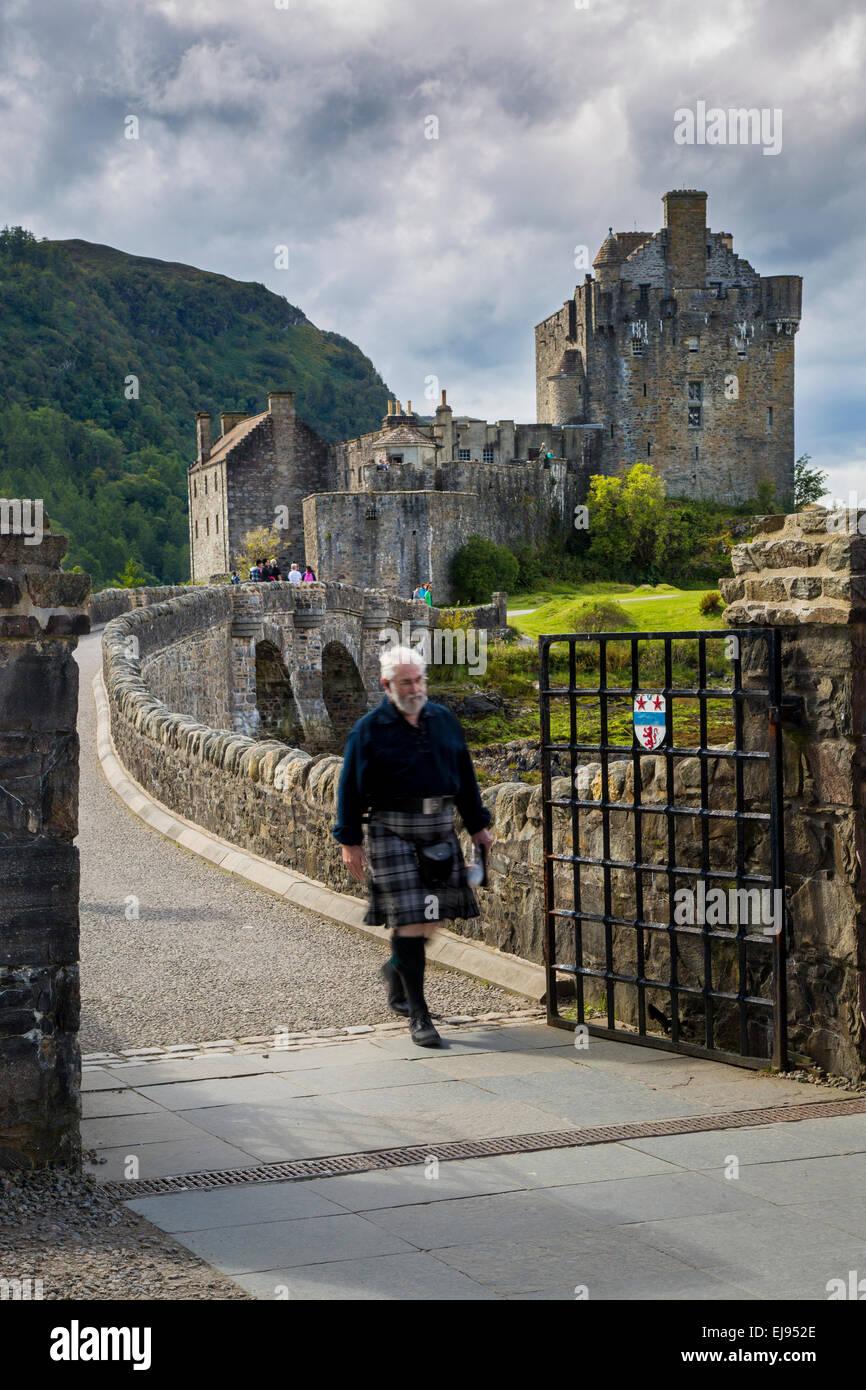 Man in a kilt walks across the bridge from Eilean Donan Castle, Highlands, Scotland, UK - Stock Image
