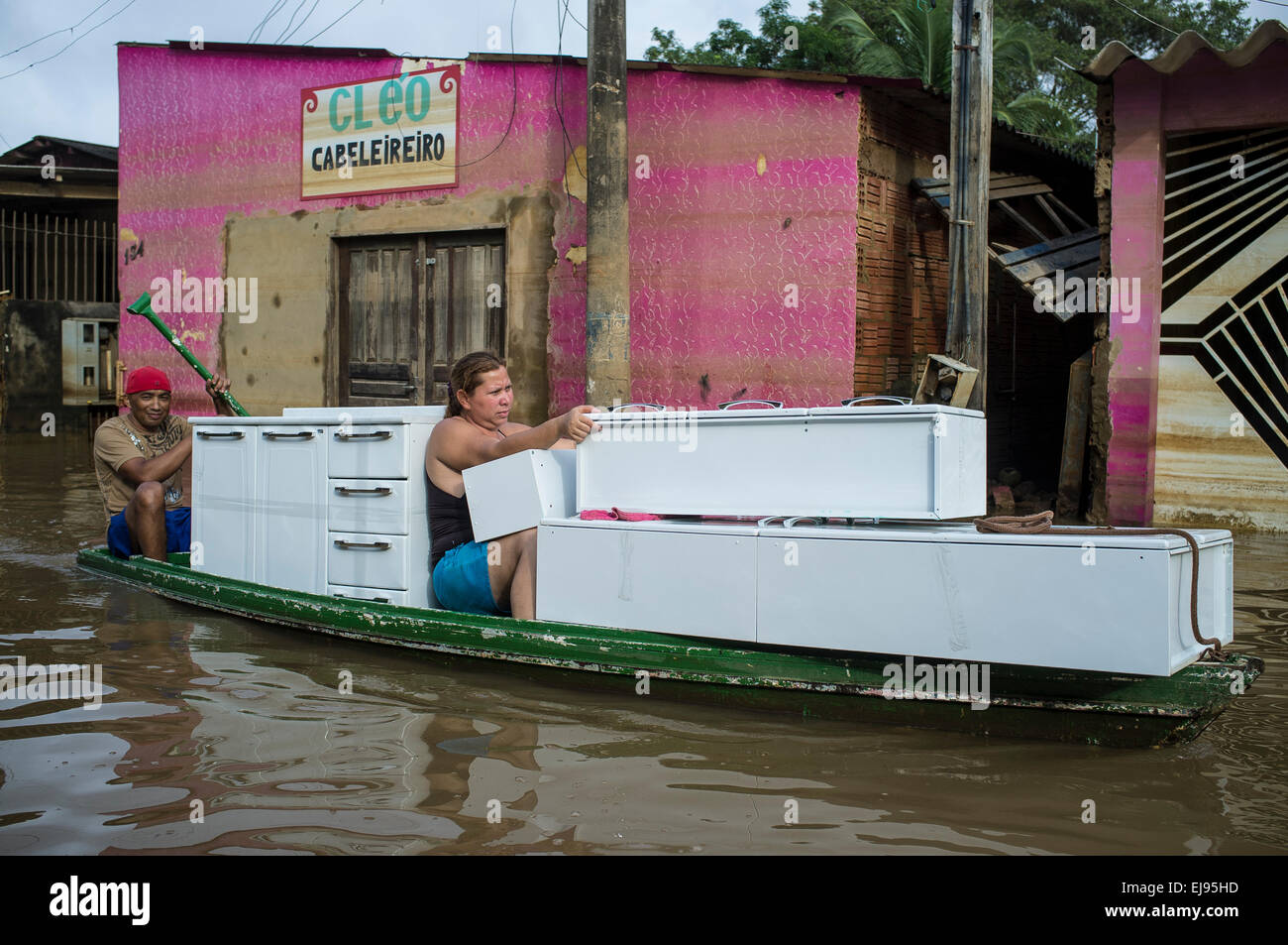 2015 flooding in Brazilian Amazon,  woman transports kitchen furniture in small boat through flooded street at Triangulo Stock Photo