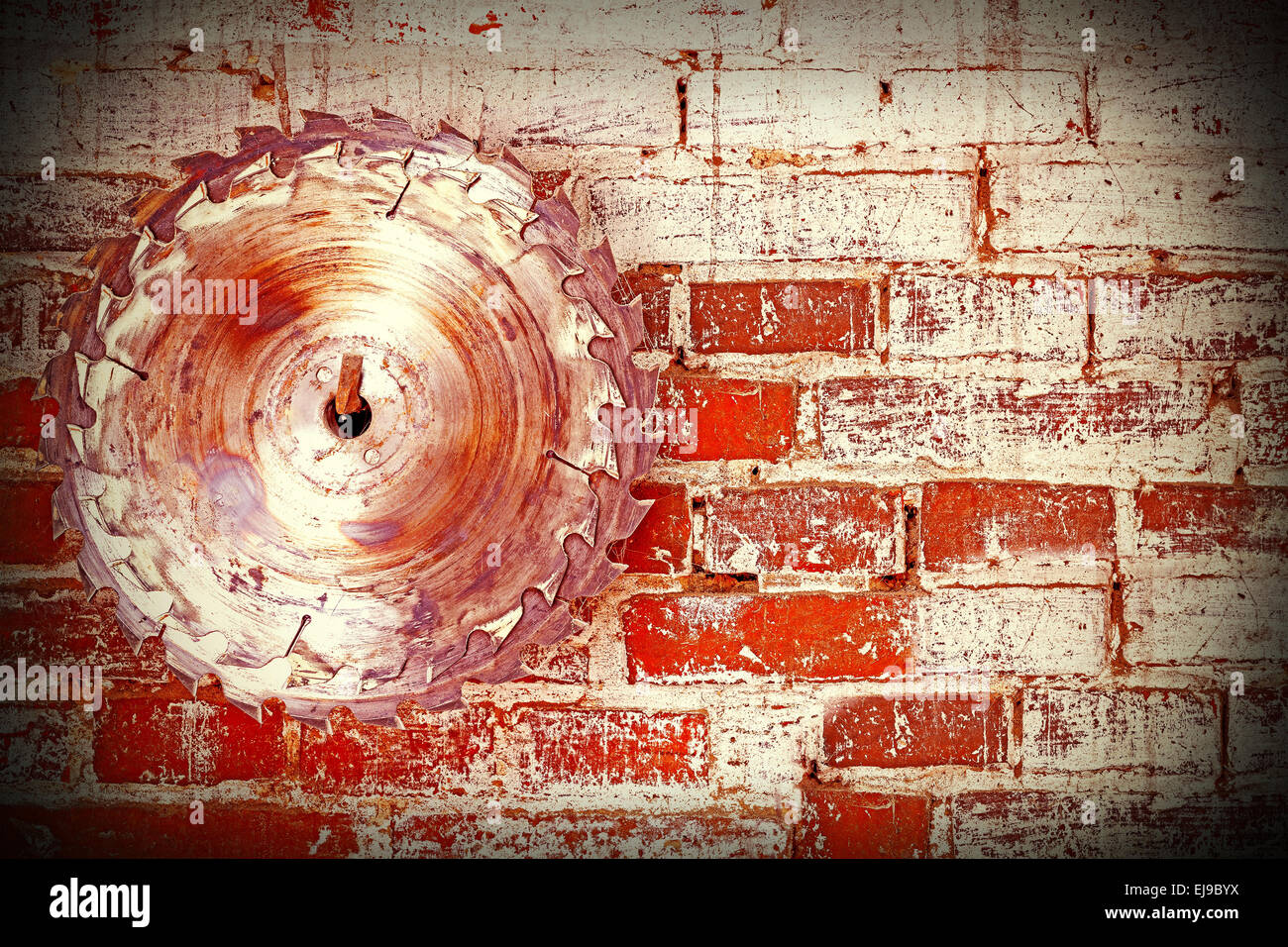 Circular saw blade on a grungy brick wall, background or texture. - Stock Image