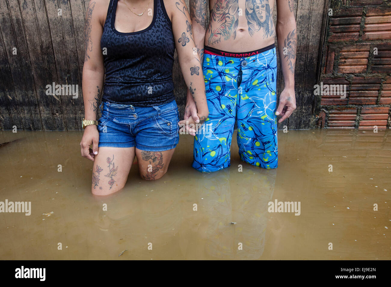 2015 flooding in Brazilian Amazon, displaced young couple in front of flooded house. Floods have been affecting - Stock Image