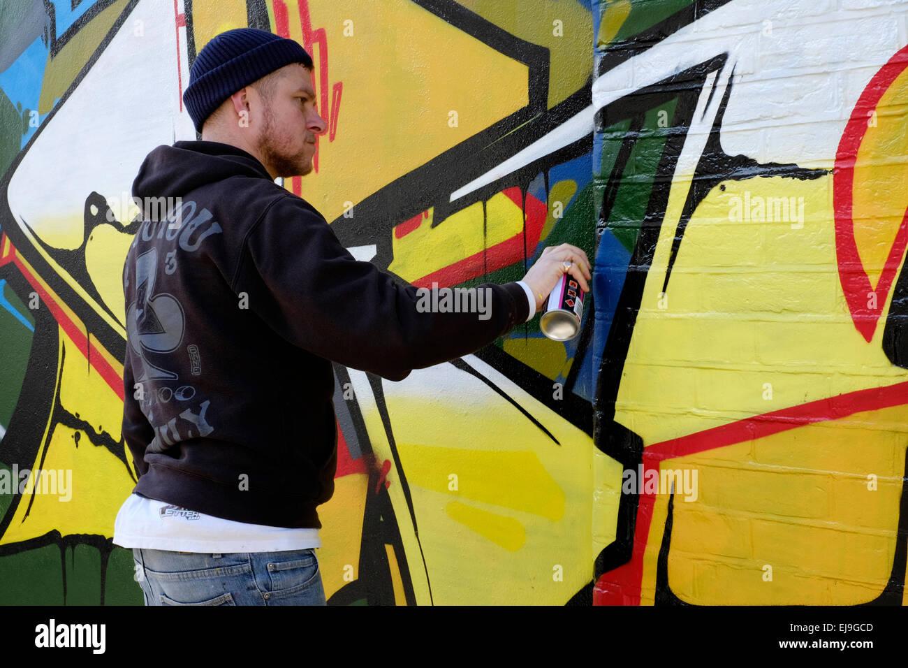 artist creating modern street art graffiti spray painted on a wall ...