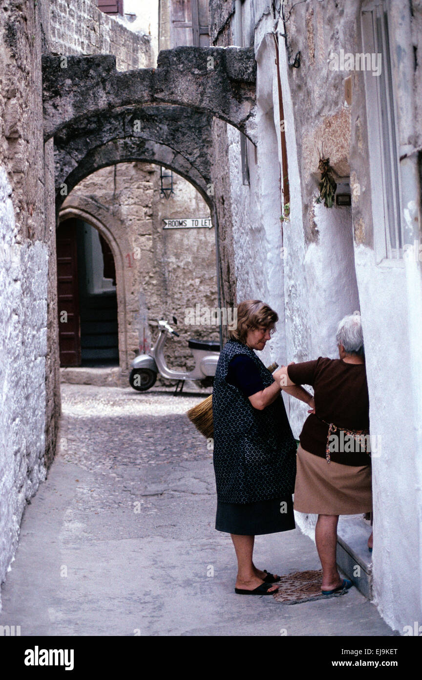 Greek Women or Neighbors Chat on Doorstep of their Traditional Houses in Rhodes Old Town Rhodes Greece - Stock Image