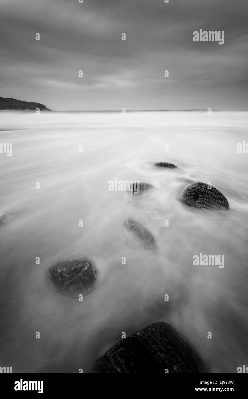 Stones lie on the beautiful sandy beach of Dail Mor as the tide comes in. Stock Photo