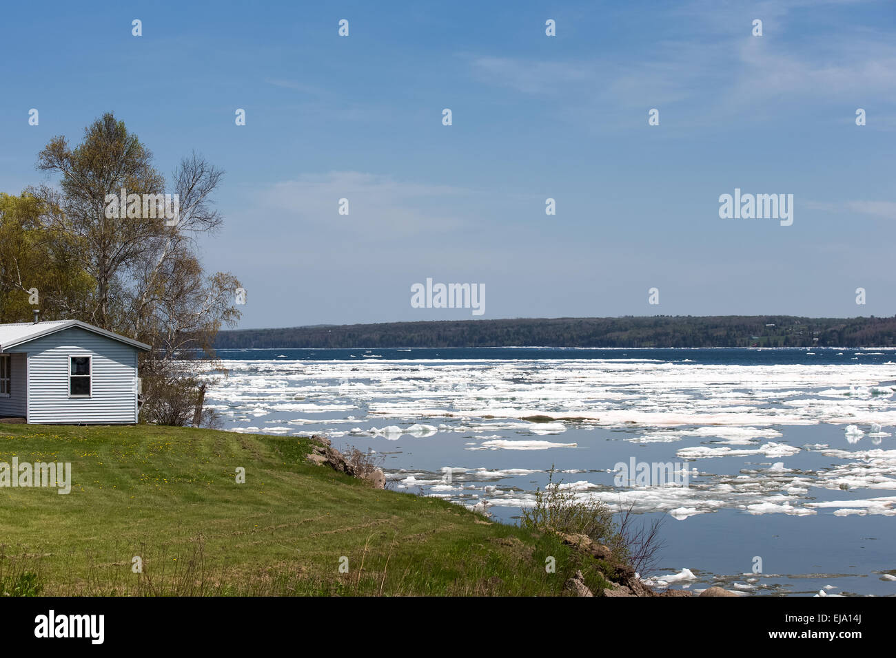 Ice breaking up on a bay in the Spring.   Small house overlooking the scene.  Copy space in upper part of frame. Stock Photo