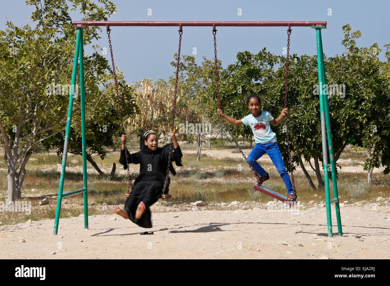 Girls playing on swings, Sultanate of Oman - Stock Image
