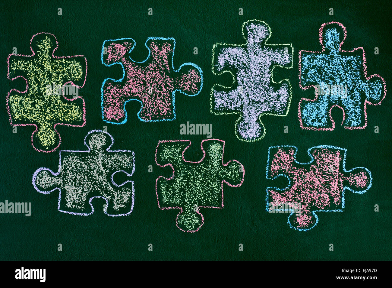 Some Puzzle Pieces Drawn With Chalk Of Different Colors On A Green