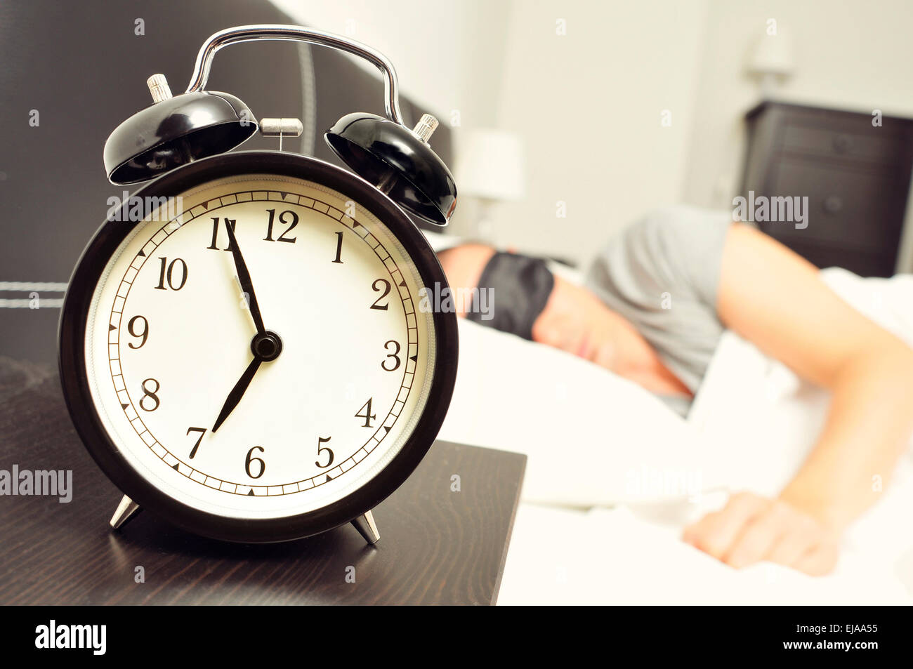Closeup Of An Alarm Clock At 6 55 In The Morning On The Night Table And A Young Caucasian Man Sleeping In Bed With A Black Sleep
