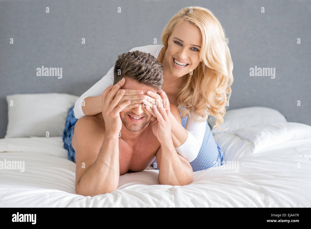 Mischievous woman covering her husbands eyes - Stock Image