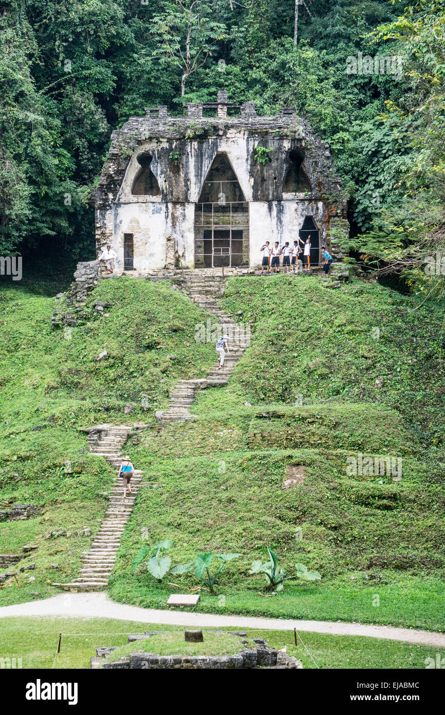 group of Mexican teen schoolboys line up outside Temple of the Foliated Cross as 2 women toil up the ascent Palenque - Stock Image
