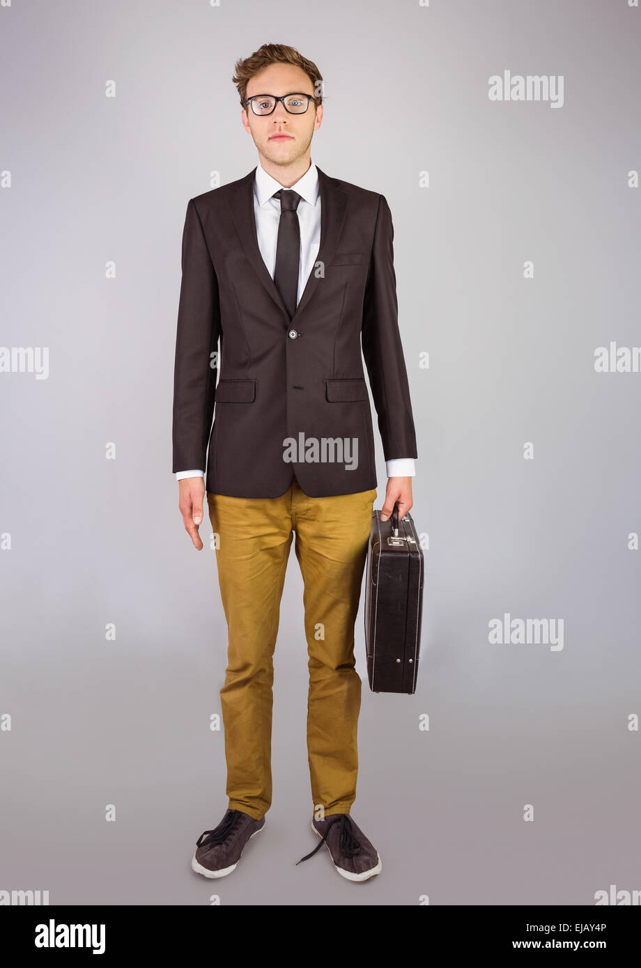 Young geeky businessman holding briefcase - Stock Image