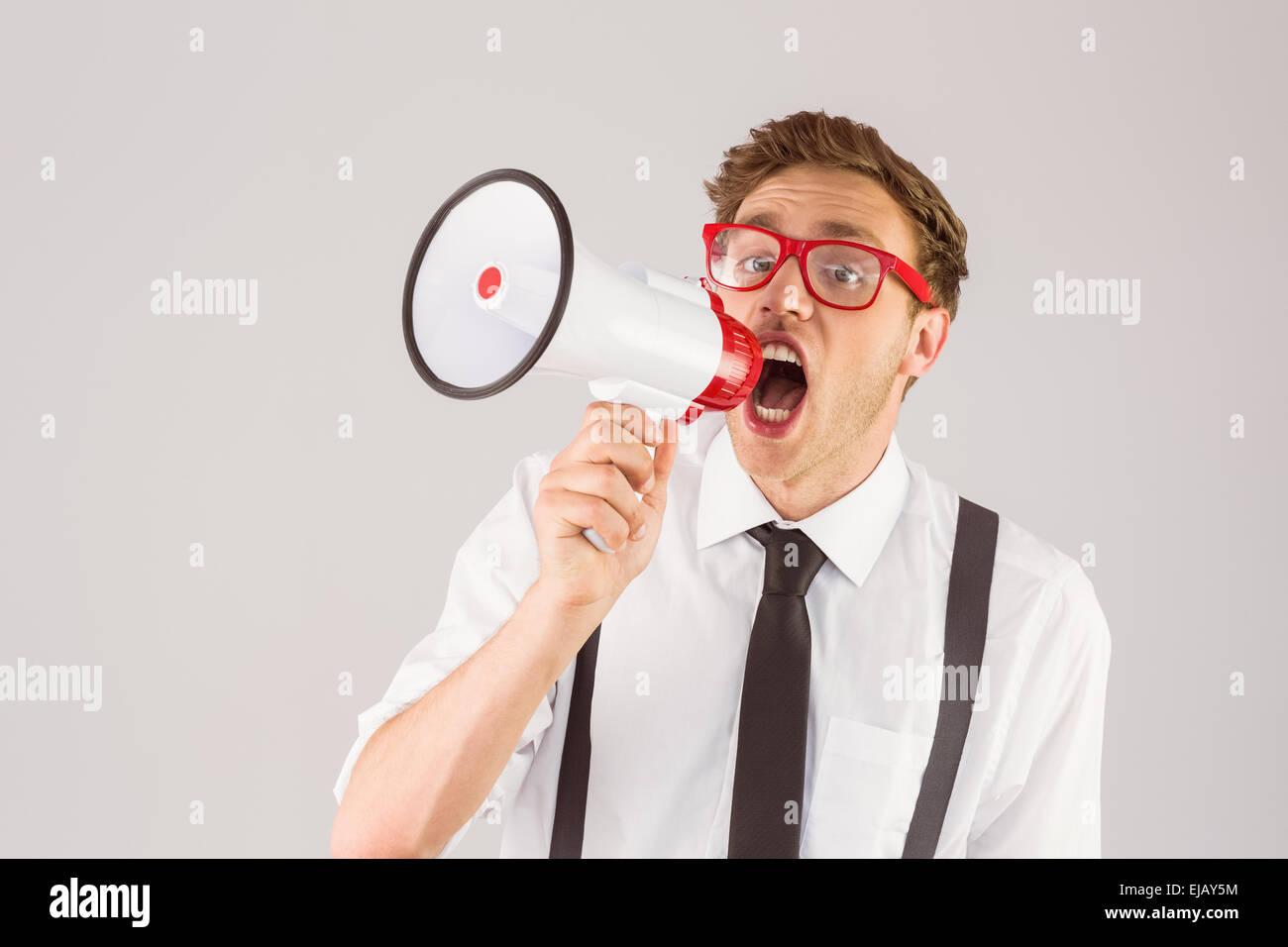 Geeky businessman shouting through megaphone - Stock Image