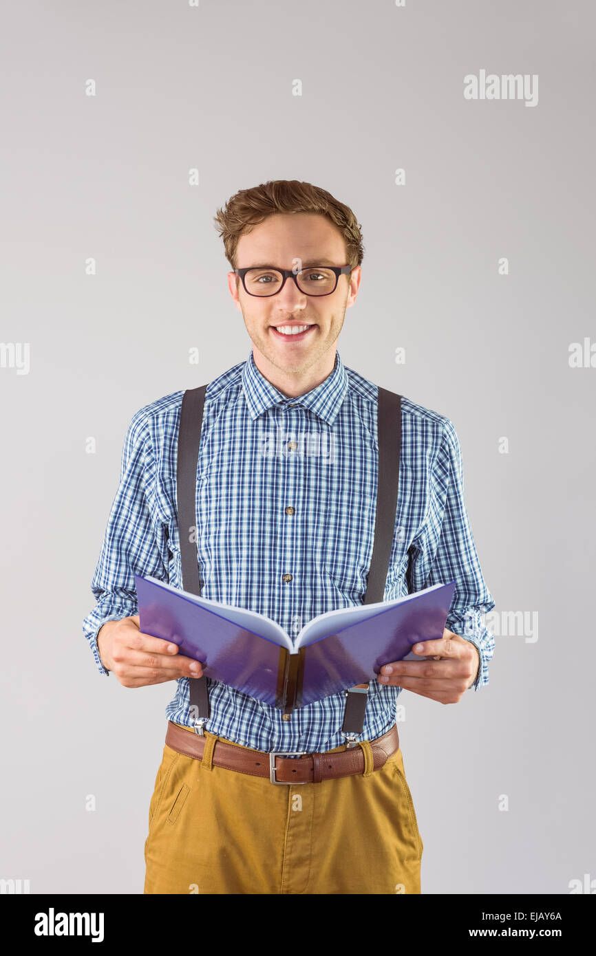 Geeky student reading a book - Stock Image