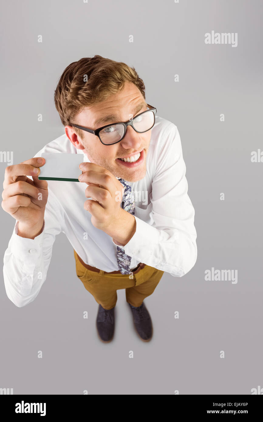 Young geeky businessman showing card - Stock Image