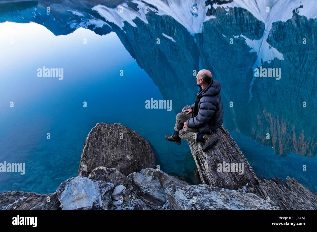 Man enjoys the calm of morning,  the Rockwall at Floe Lake, Kootenay National Park, British Columbia, Canada - Stock Image