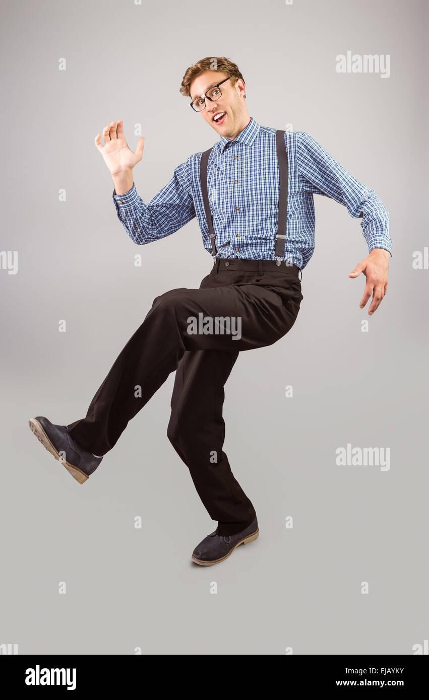 Geeky hipster walking and looking at camera - Stock Image
