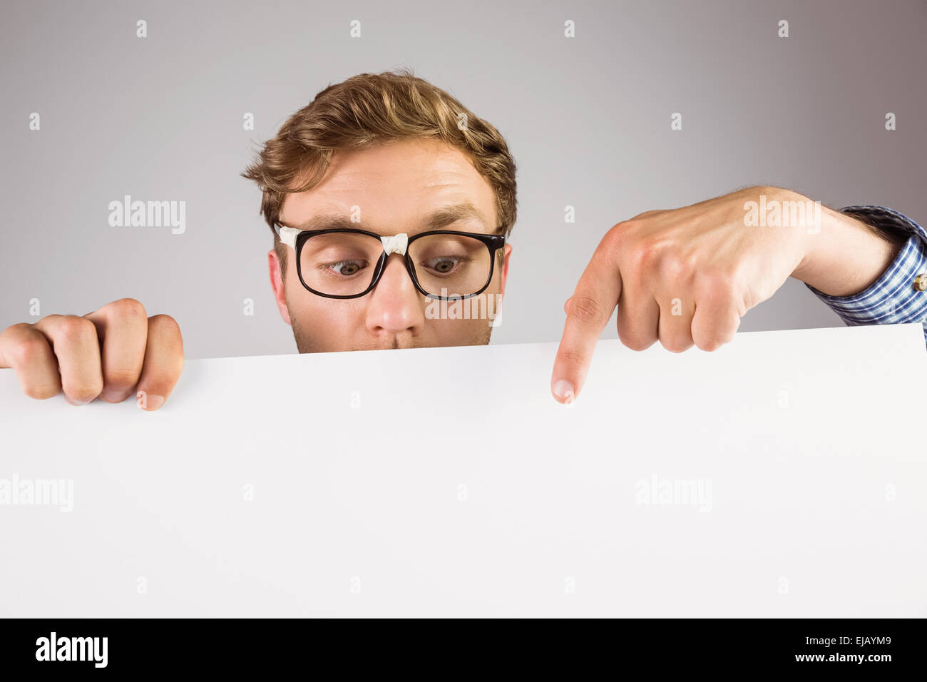 Geeky hipster showing a card - Stock Image
