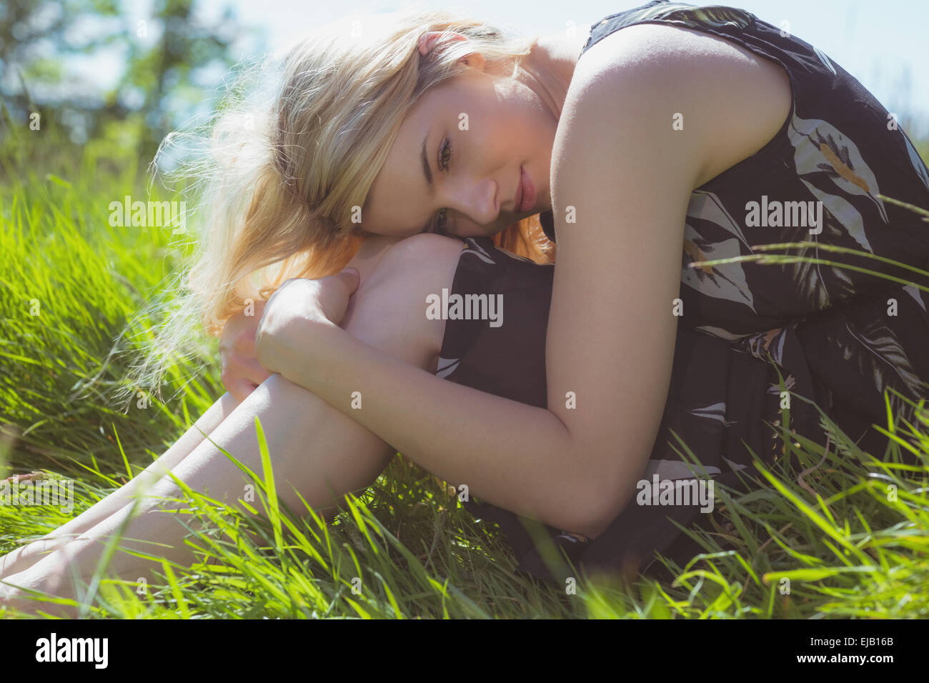 Pretty blonde in sundress sitting on grass - Stock Image