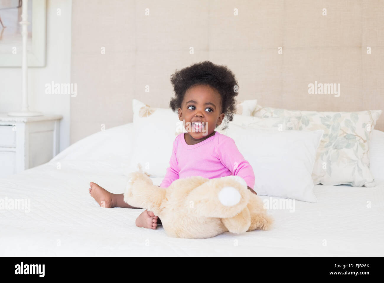 Baby girl in pink babygro sitting on bed - Stock Image