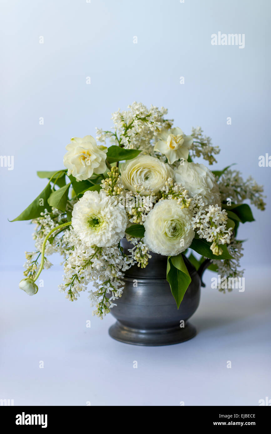Spring flower arrangement with white ranunculus and lilac blossoms - Stock Image