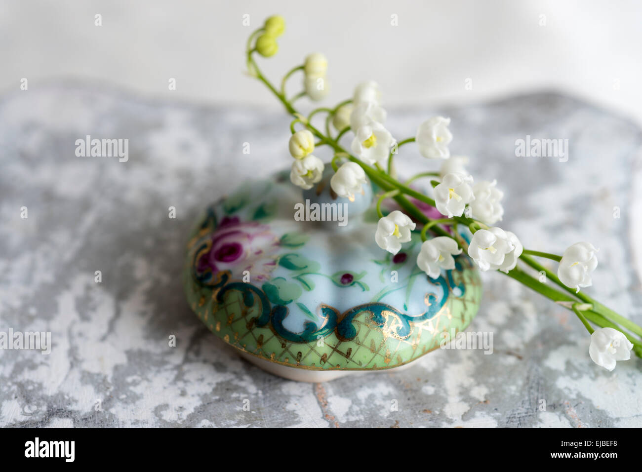 Lily of the Valley flowers (Convallaria majalis) with hand painted lid of bowl - Stock Image