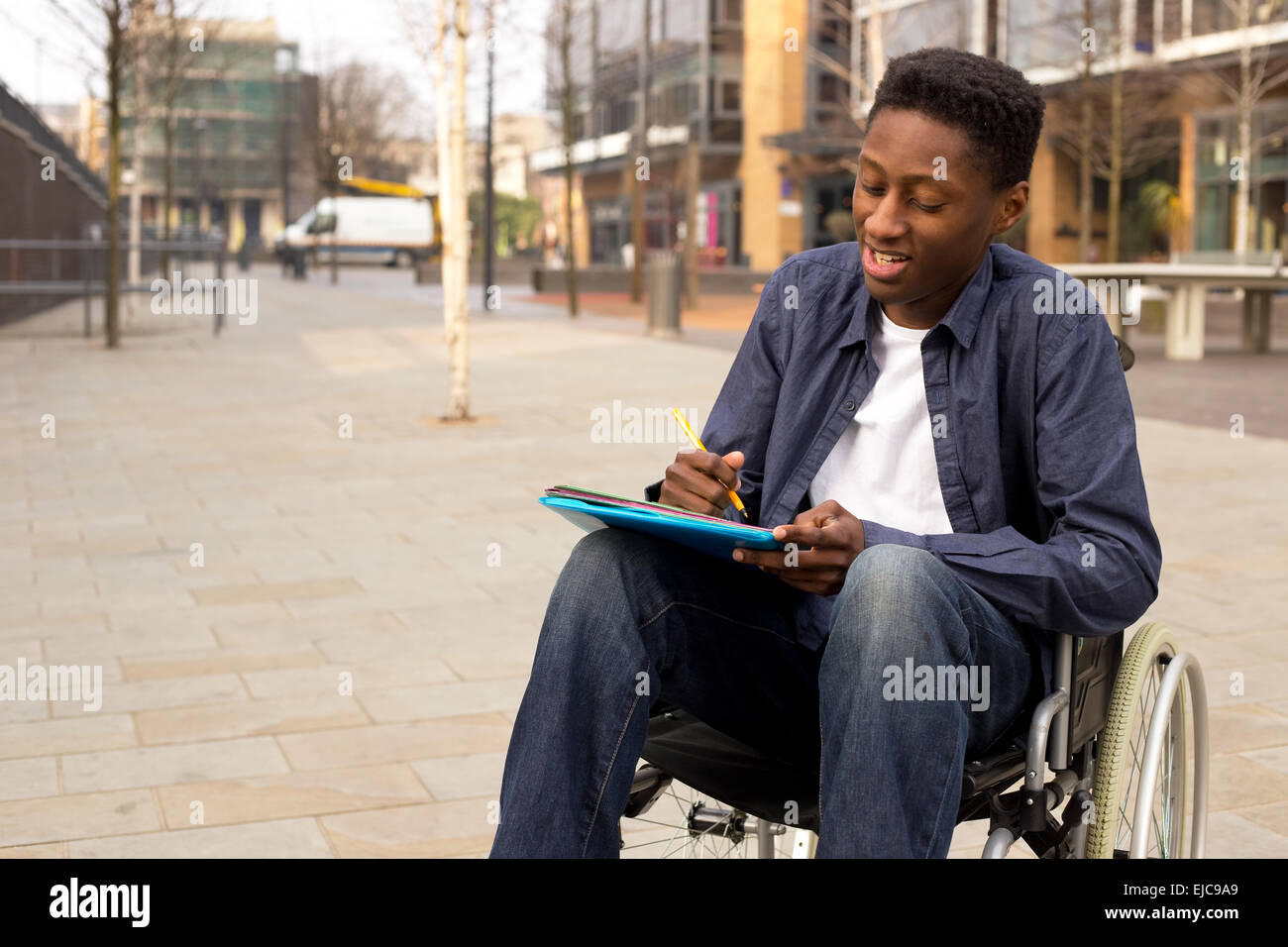young man in a wheelchair writing a letter - Stock Image