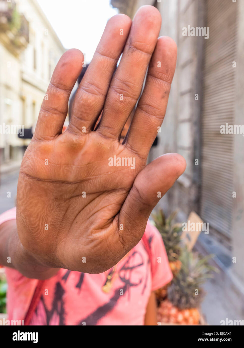 "An Afro-Cuban man holds up his outstretched hand to block the lens of a camera to indicate ""no photos!"" Stock Photo"