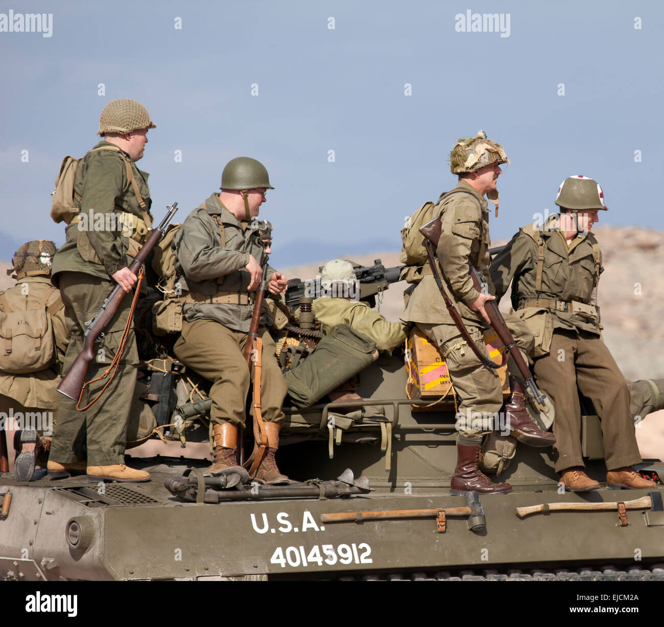 us army troops sitting on tank wearing world war ii uniforms and