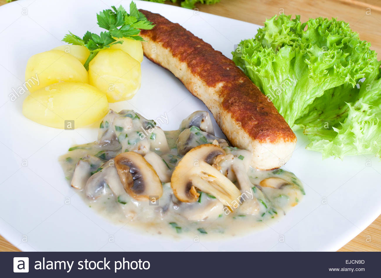 Grilled sausage on potatoes and mushrooms Stock Photo