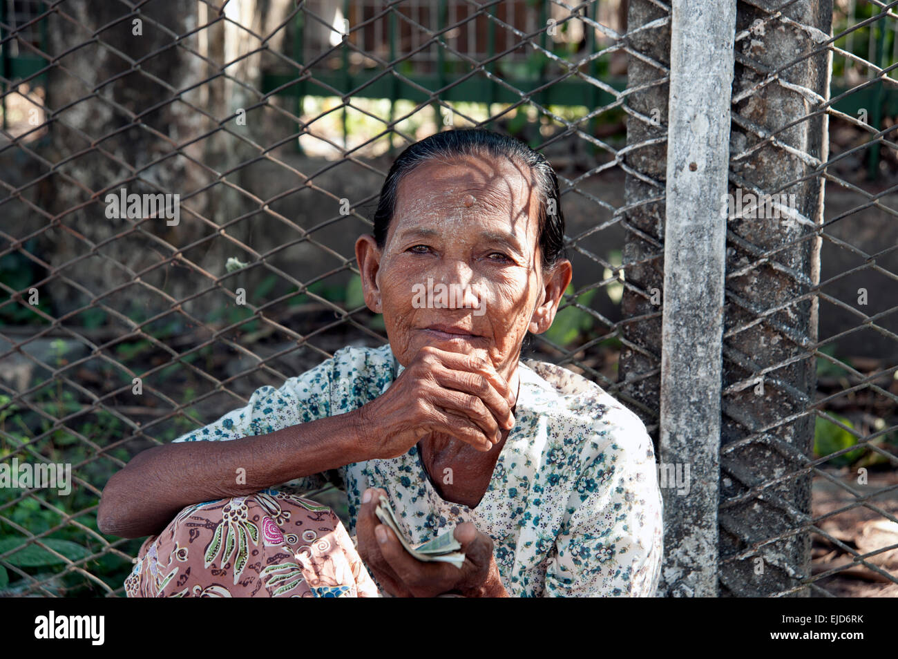An old Burmese lady begging sitting on the pavement against a wire ...