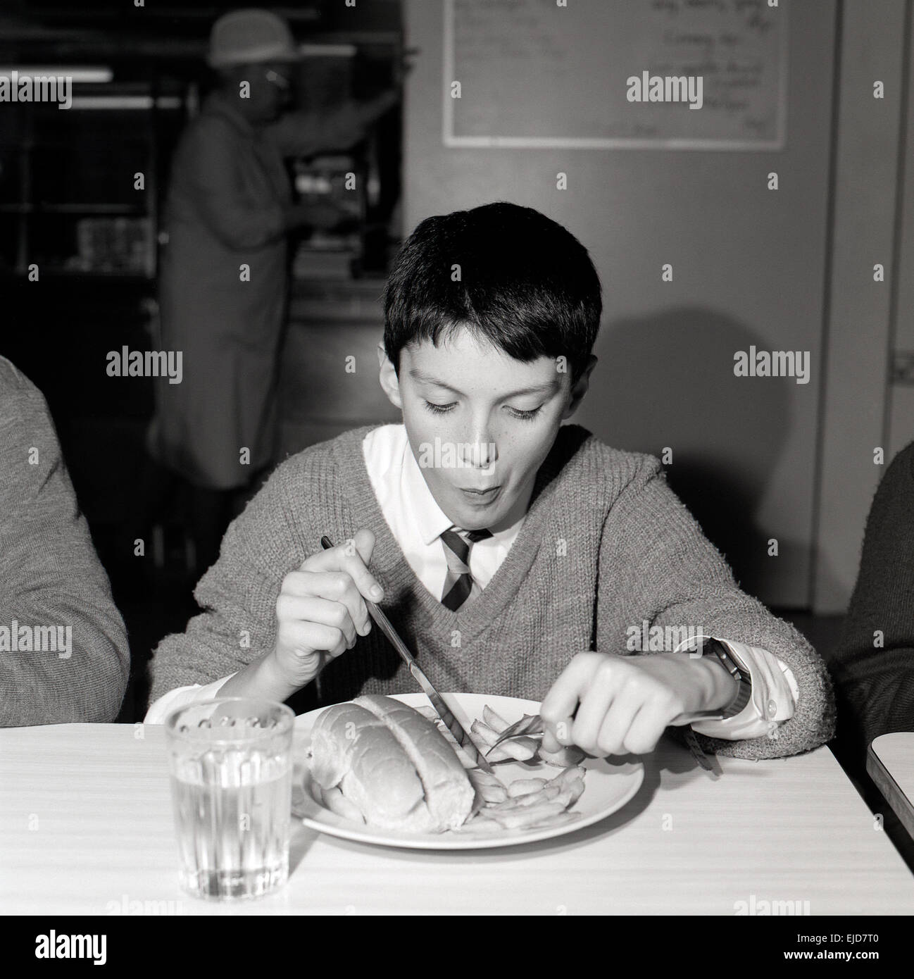 A black and white 1990s archival image of a boy wearing a school uniform sitting at a table eating school dinner - Stock Image