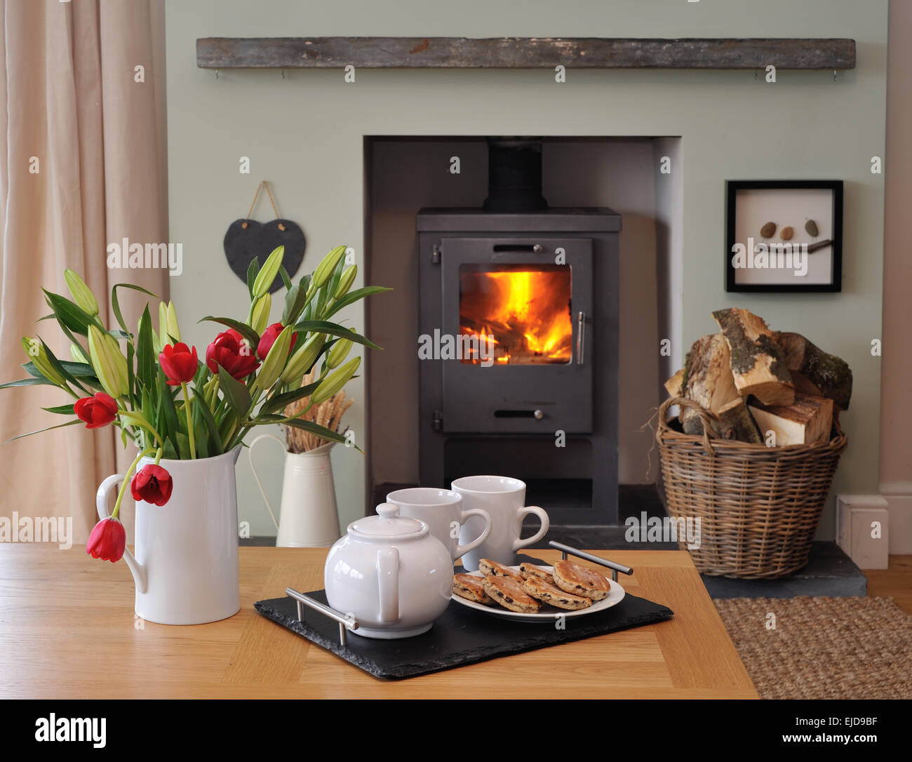 Interior design fireplace with vase of flowers and tea - Stock Image