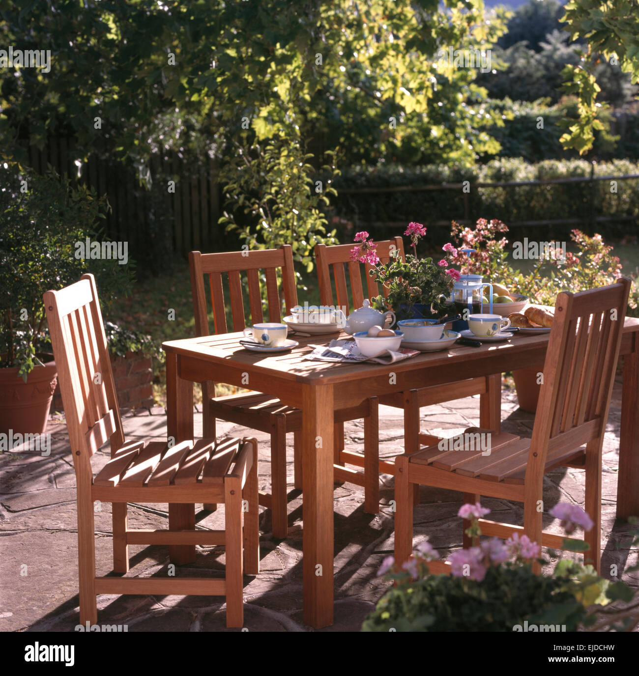 Wooden chairs at table set for lunch on sunlit patio in country garden & Wooden chairs at table set for lunch on sunlit patio in country ...