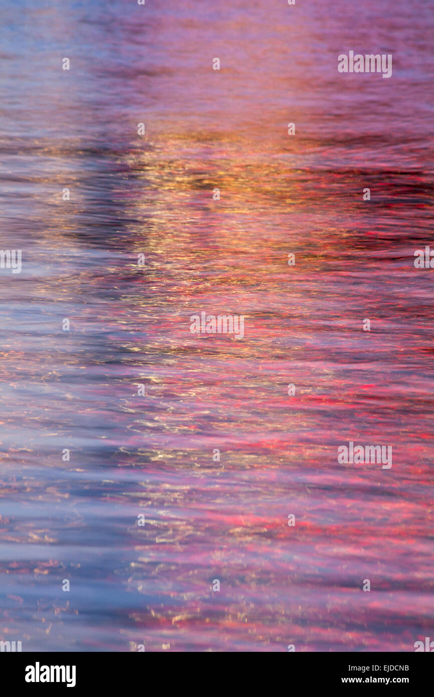 abstract patterns of colourful lights at dusk reflections in moving water - Stock Image