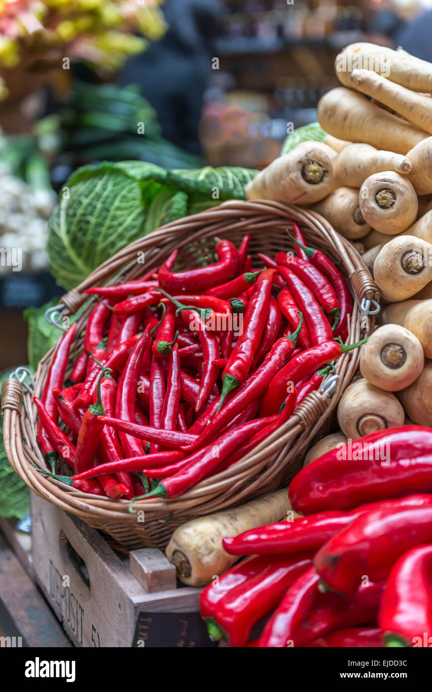 A basket of red chillies displayed on a vegetable stall against a backdrop of parsnips and cabbage Stock Photo