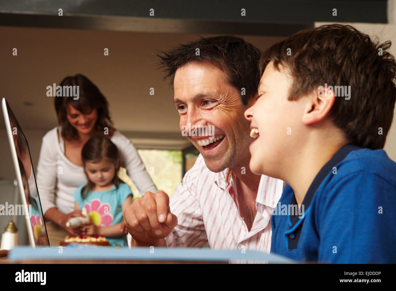 A family, two parents and two children together at home. A father and son on a laptop, and mother and daughter icing - Stock Image