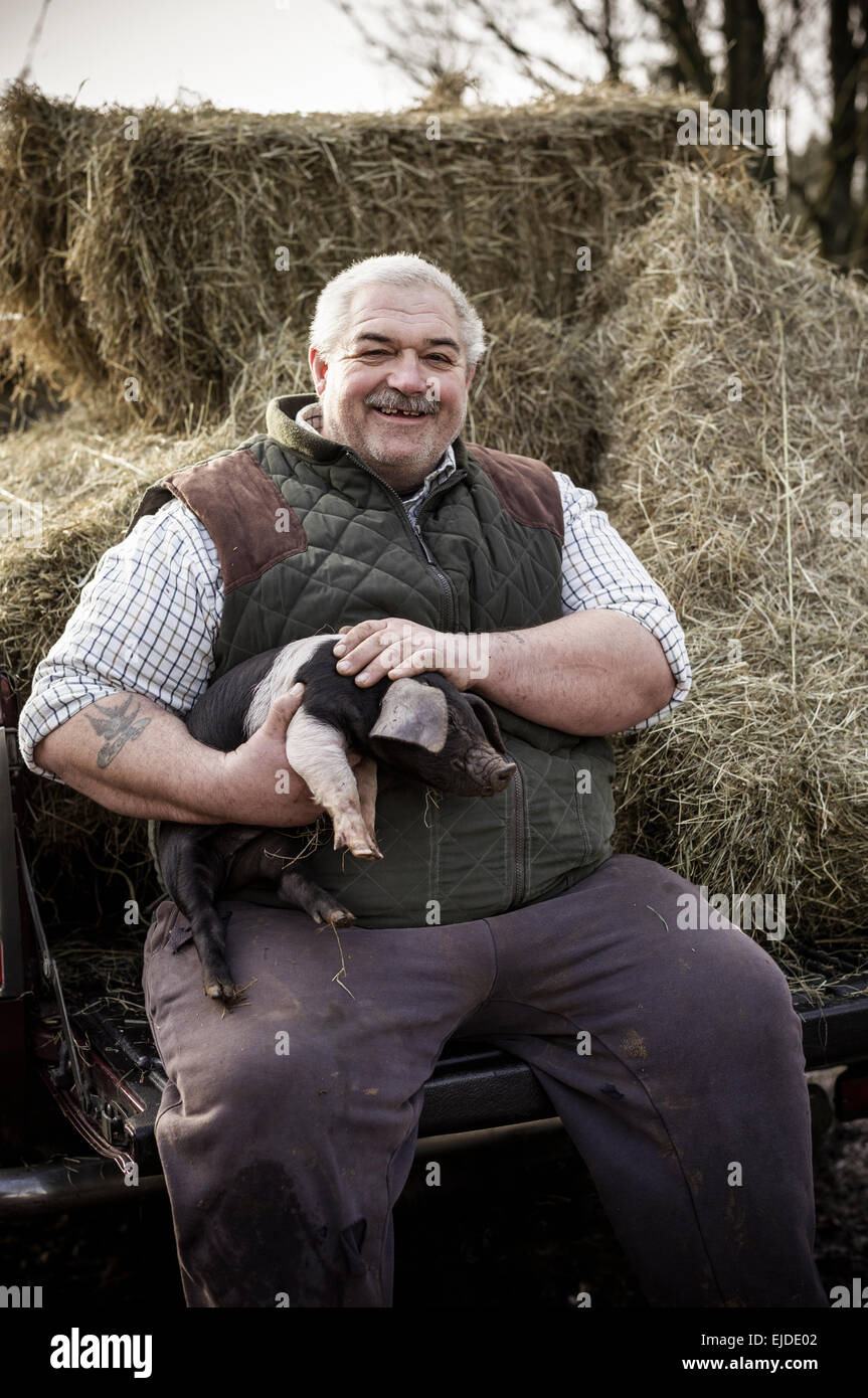 A large man, farmer in a waistcoat and working clothes, holding a piglet and smiling - Stock Image