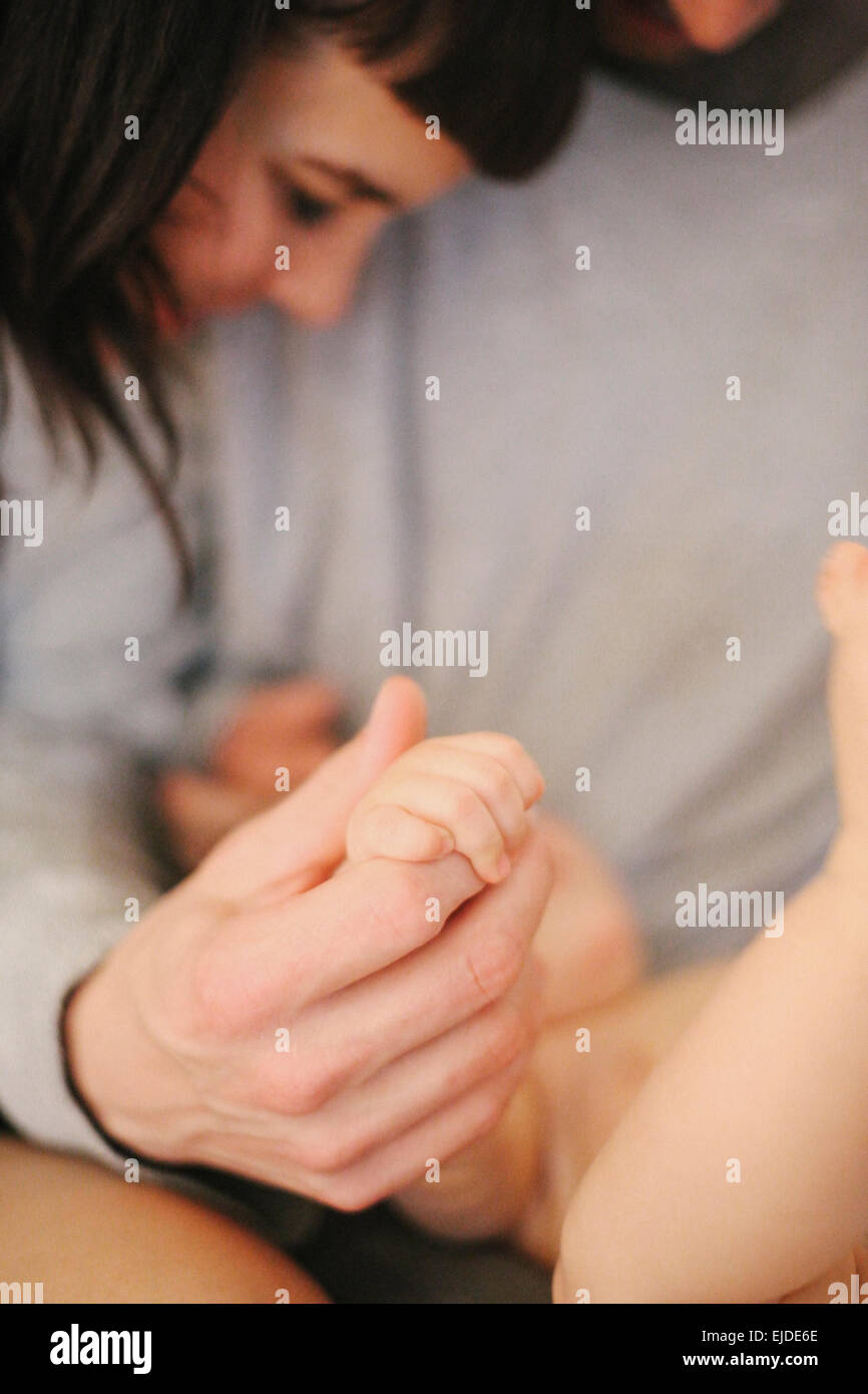 A father's hand clasping a young baby's small hand in his. - Stock Image
