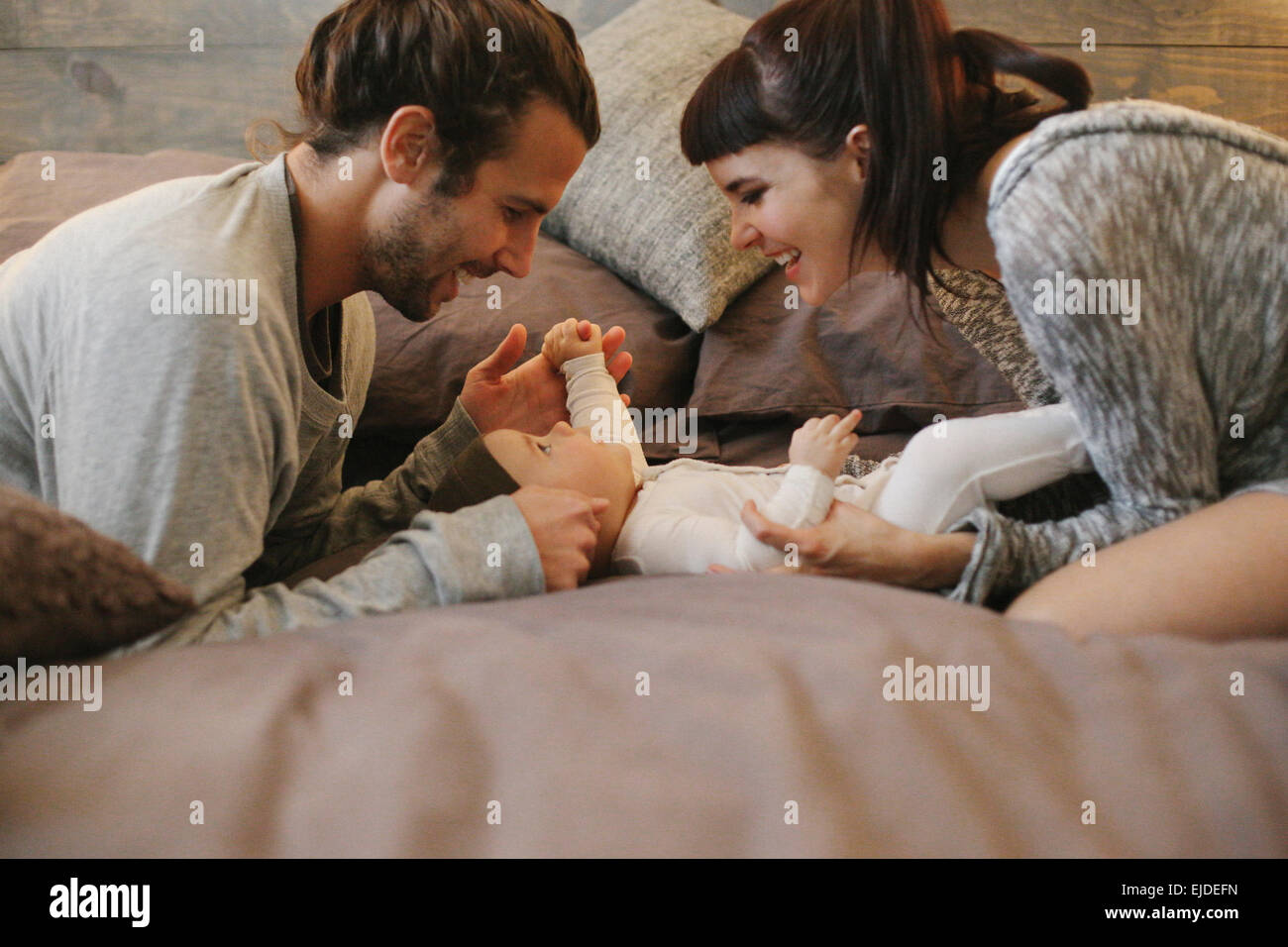 A mother, father and young baby together at home. - Stock Image