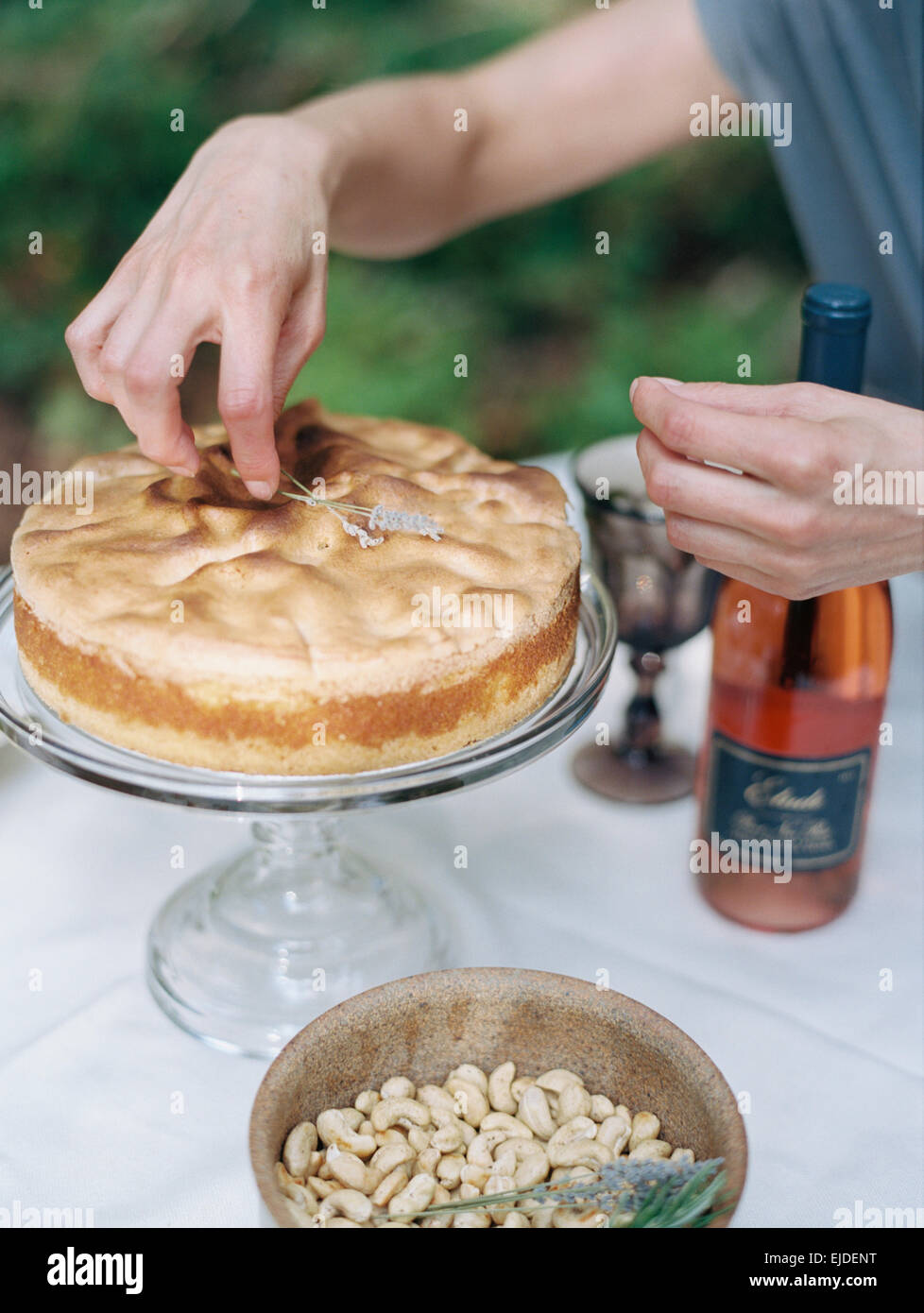 A woman decorating a cake on a glass stand. A dish of nuts and a bottle of rose wine. - Stock Image