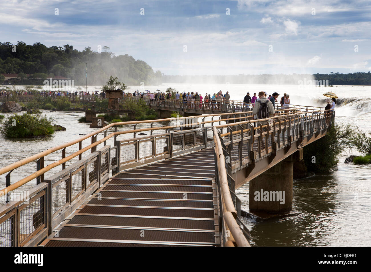 Argentina, Iguazu Falls National Park, tourists viewing Garganta el Diablo waterfall, from elevated walkway - Stock Image