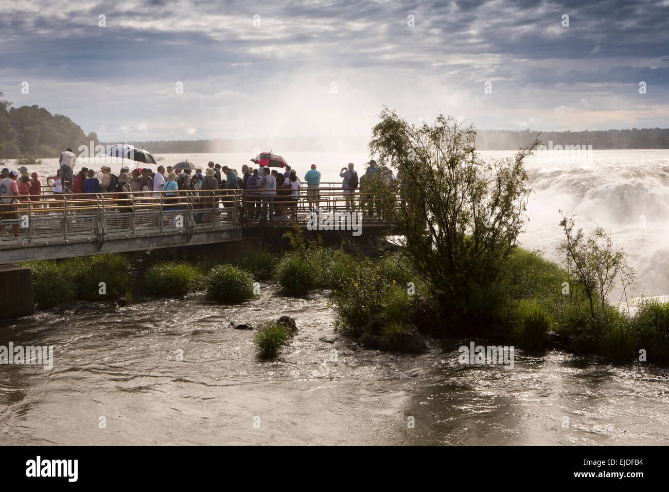 Argentina, Iguazu Falls National Park,tourists viewing Garganta el Diablo waterfall, from elevated walkway - Stock Image
